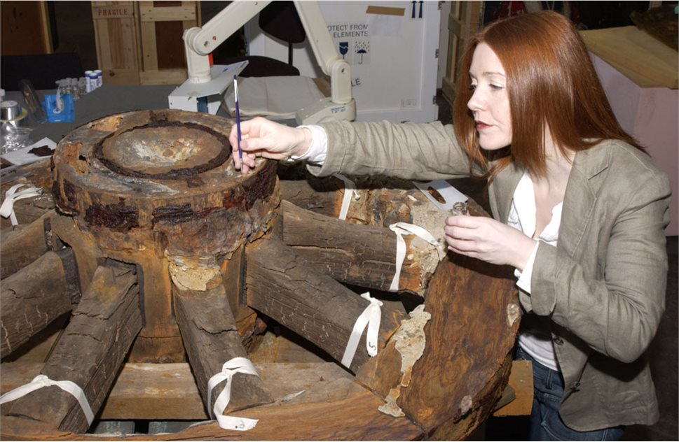 Image: Joanne Lowe, Ulster Museum conservation department working on one of the original large carriage wheels. Replicas of the wheels and carriage were made to display the guns in both museums.