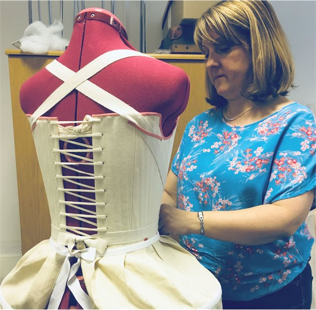 Image: Joanne Pollock at work in the period costume workroom, making a replica of a 1760s dress in the UFM collection, complete with corset and petticoat. © National Museums Northern Ireland