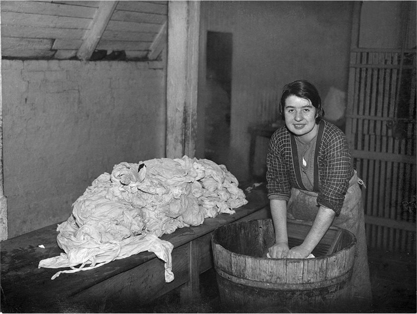 Image: A woman washing clothes by hand using a wash board in a wooden tub, 1941. HOYFM.BT.1201 © National Museums Northern Ireland.