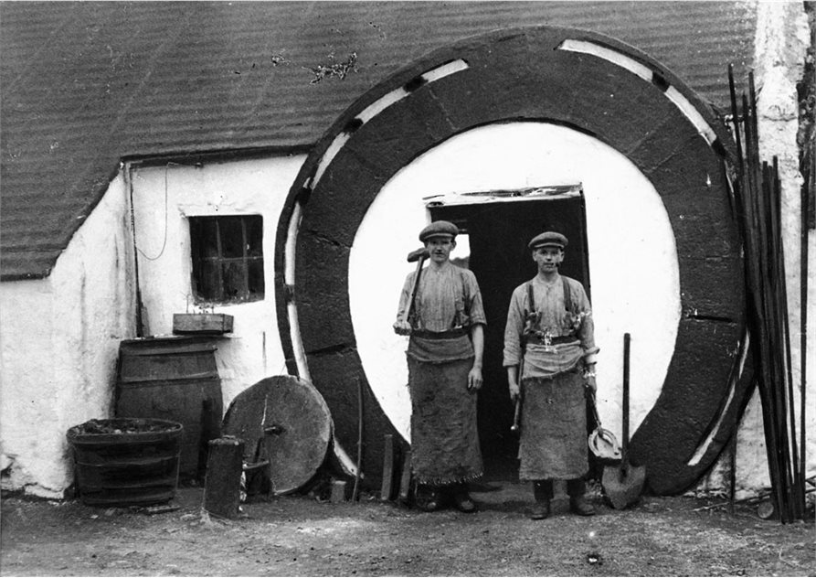 Image: Two blacksmiths standing outside the horseshoe shaped entrance to their forge, 1925. HOYFM.BT.1251 © National Museums Northern Ireland.