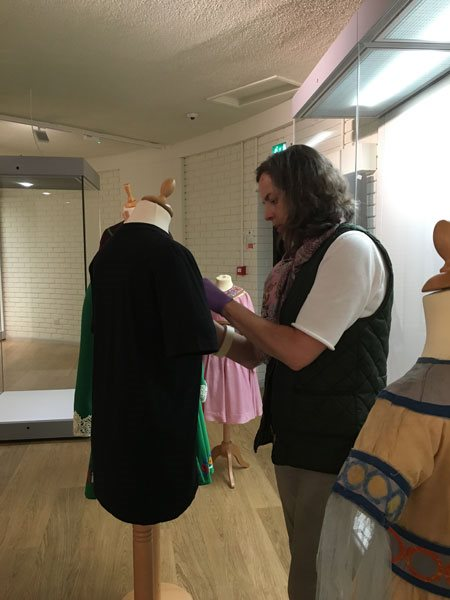 Image: National Museums NI Care of Collections officer Julie Anne Tolerton adjusts costume in the exhibition gallery before it goes on display.