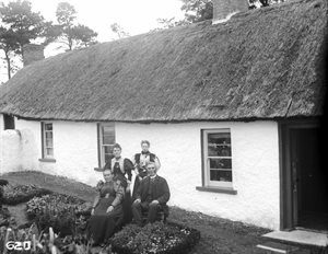 Group outside thatched cottage