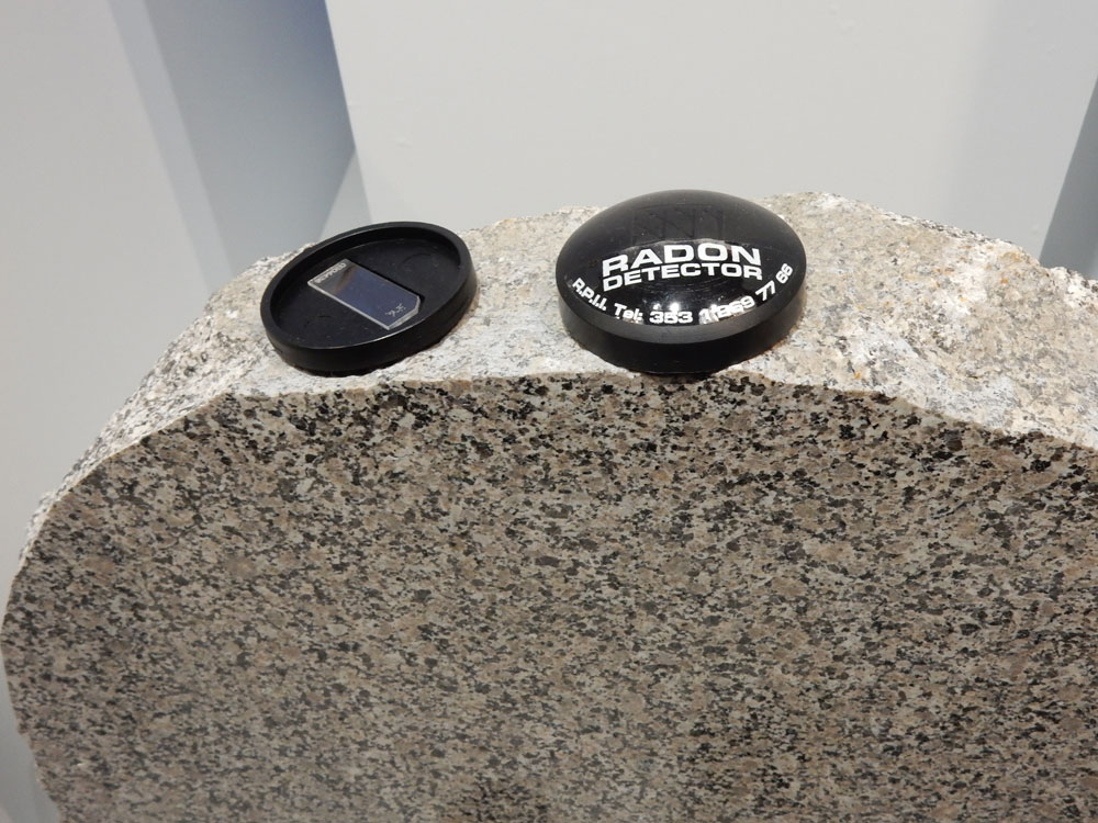 A headstone of Mournes granite, with two radon detectors. Radon can be detected by looking for microscopic damage to the clear plastic strip in the open detector on the left.