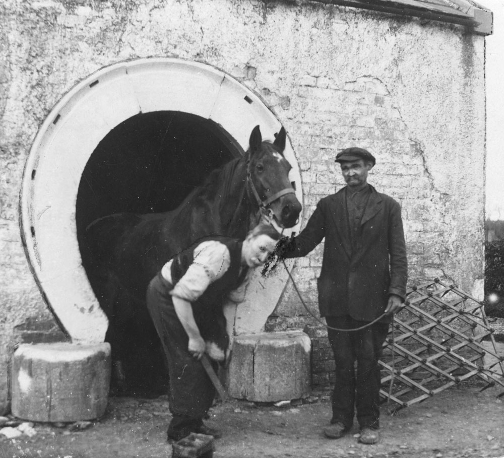 A farrier working with a horse outside his forge. HOYFM.BT.1487 © National Museums Northern Ireland